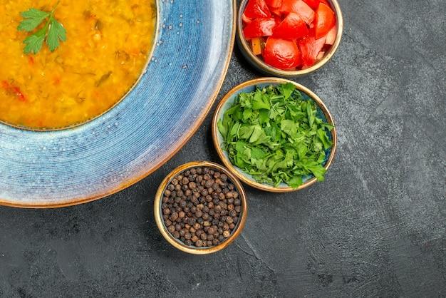 Bovenste close-up weergave linzensoep kom linzensoep tomaten specerijen kruiden