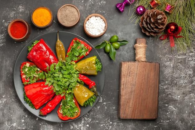 Bovenste close-up weergave paprika houten bord plaat van paprika kerstboom speelgoed kleurrijke kruiden