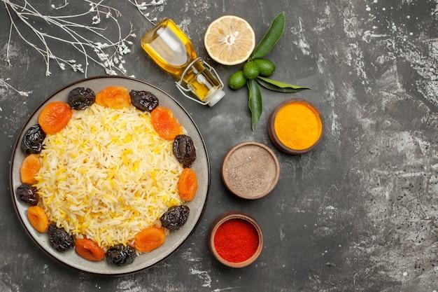 Bovenste close-up weergave rijst fles olie citrusvruchten plaat rijst met gedroogde vruchten kruiden