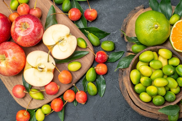 Bovenste close-up weergave vruchten rode appels op het bord kersen en citrusvruchten in kom