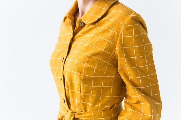 Bovenste deel van gele jurk op witte muur.