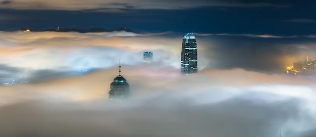 Bovenste delen van wolkenkrabbers 's nachts bedekt met mist
