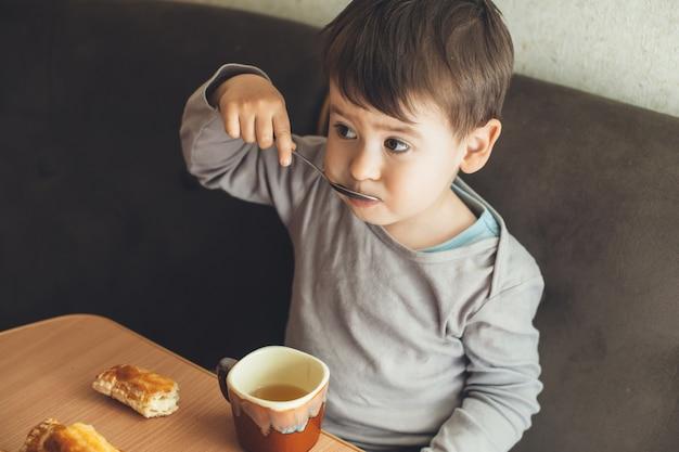 Bovenste foto van een kleine blanke brunette jongen die een thee met een lepel aan de tafel drinkt en wat koekjes eet