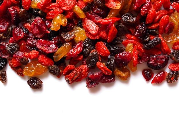 Bovenste frame van gedroogde granen natuurvoeding met gojibes en droge rozijnen druivenfruit op wit.
