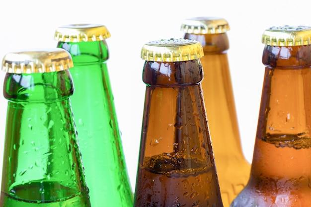 Bovenste gedeelte van flessen gekleurd glas met druppels water
