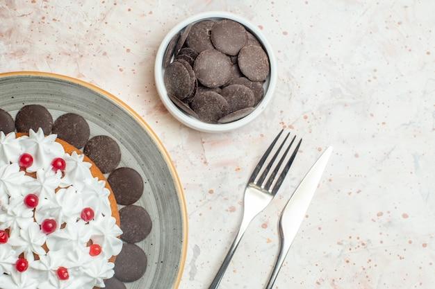 Bovenste halve cake met banketbakkersroom op ovale plaatchocolade in komvork en dinermes