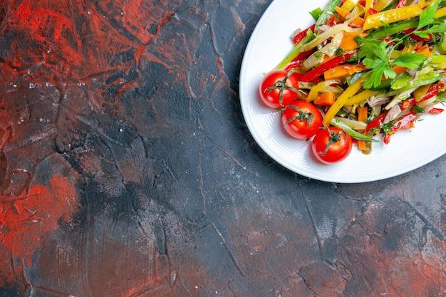 Bovenste halve groentesalade op ovale plaat op donkere vrije plaats
