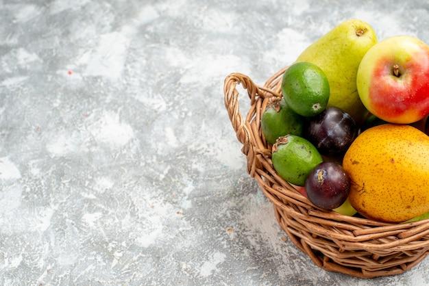 Bovenste halve plastic rieten mand met appelperen, feykhoas pruimen en persimmon aan de rechterkant van de grijze tafel