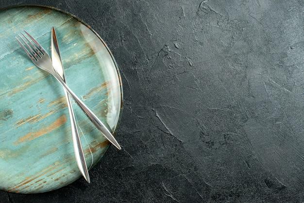 Bovenste halve weergave gekruist mes en vork op ronde schotel op zwarte tafel kopie plaats