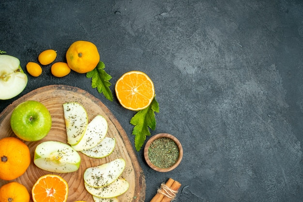 Bovenste halve weergave gesneden appels en mandarijnen op rustieke serveerplank kaneel gedroogde muntpoederkom cumcuat op donkere tafel met kopieerplaats