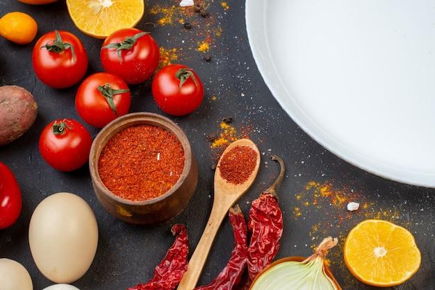 Bovenste halve weergave ronde plaat knoflook rode peper poeder in kleine kom tomaten eieren op tafel