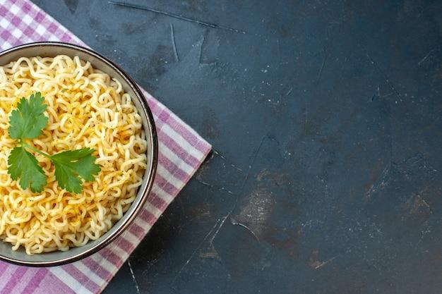 Bovenste helft aziatische ramen noodles in kom op roze wit geruite keukenhanddoek op donkere tafel met kopieerplaats