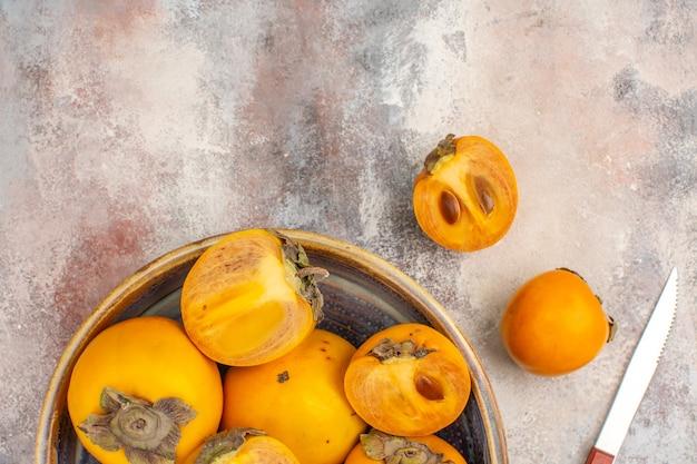 Bovenste helft bekijk heerlijke dadelpruimen in een kom persimmon en mes op naakte achtergrond