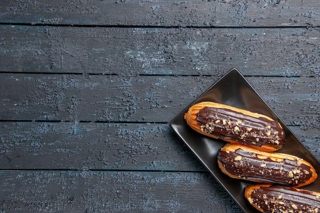 Bovenste helft chocolade-eclairs op rechthoekige plaat aan de rechterkant van de donkere houten tafel