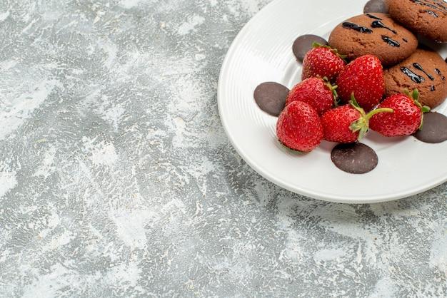 Bovenste helft chocoladekoekjes aardbeien en ronde chocolaatjes op het witte ovale bord rechtsboven op de grijswitte ondergrond
