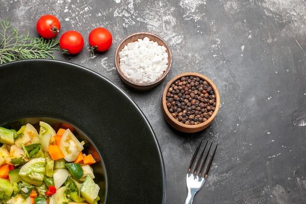 Bovenste helft groene tomatensalade op ovale plaat een vork verschillende kruiden op donkere achtergrond