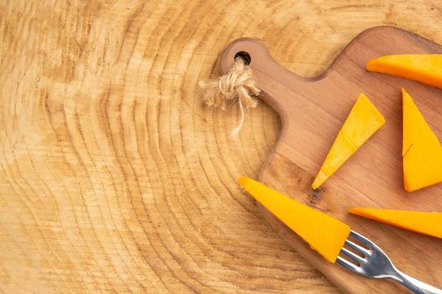 Bovenste helft kaas op vork plakjes kaas op snijplank op houten tafel