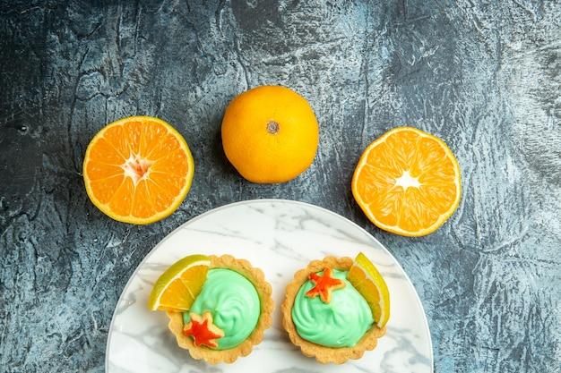Bovenste helft kleine taartjes met groene banketbakkersroom en een schijfje citroen op plaat gesneden sinaasappelen op donkere ondergrond