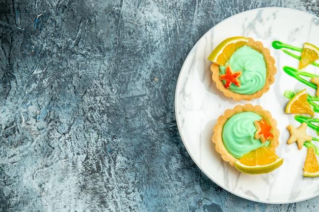 Bovenste helft kleine taartjes met groene banketbakkersroom en schijfje citroen op plaat op donkere oppervlak vrije plaats bekijken