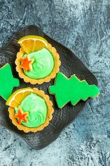 Bovenste helft kleine taartjes met groene banketbakkersroom kerstboom koekjes op zwarte plaat op grijze ondergrond