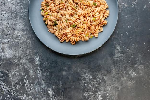 Bovenste helft rotini-pasta op ronde plaat op een donkere plaats Gratis Foto