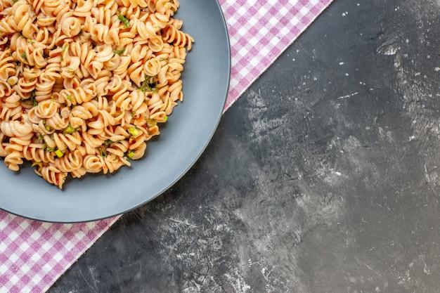 Bovenste helft rotini pasta op ronde plaat op roze wit geruit servet op grijze tafel met kopie plaats