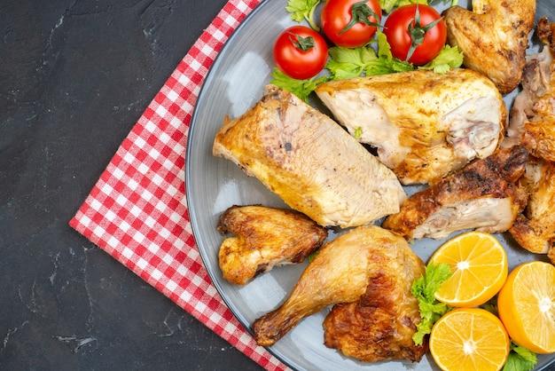 Bovenste helft uitzicht gebakken kip verse tomaten schijfjes citroen op servet op zwarte tafel
