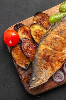 Bovenste helft van de weergave vis bak gebakken aubergines ui op houten serveerplank op donkere ondergrond