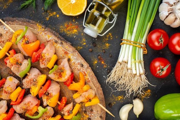 Bovenste helft van rauwe kipspiesjes op natuurlijk houten bord en verse groenten op donker