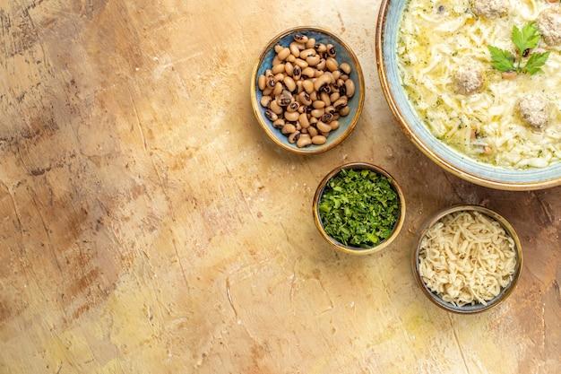 Bovenste helft weergave azerbeidzjaanse erishte in kom verschillende voeders in kommen op beige achtergrond