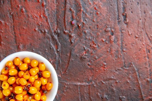 Bovenste helft weergave duindoorn in witte kom op donkerrode tafel kopie ruimte