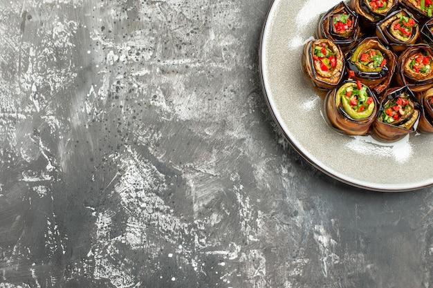 Bovenste helft weergave gevulde aubergine rollen op grijze achtergrond