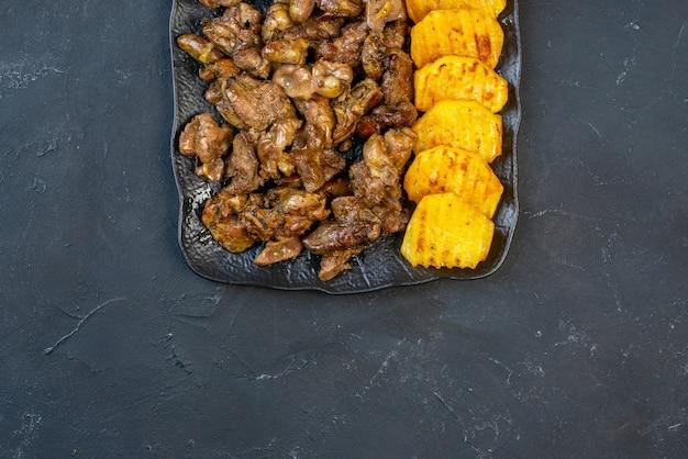 Bovenste helft weergave kippenleverbak met aardappel op zwarte plaat op tafel