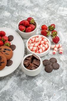 Bovenste helft weergave koekjes aardbeien en ronde chocolaatjes op de witte ovale plaat en kommen met snoep aardbeien chocolaatjes op de grijs-witte tafel
