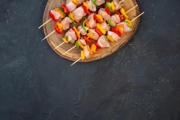 Bovenste helft weergave rauwe kip spies op houten bord op tafel