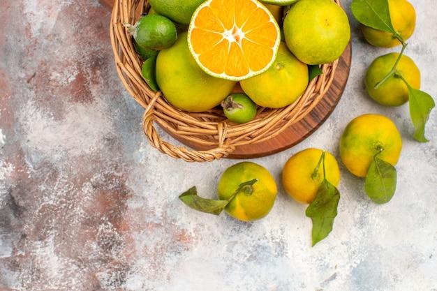 Bovenste helft weergave verse mandarijnen in rieten mand op een snijplank op naakte achtergrond