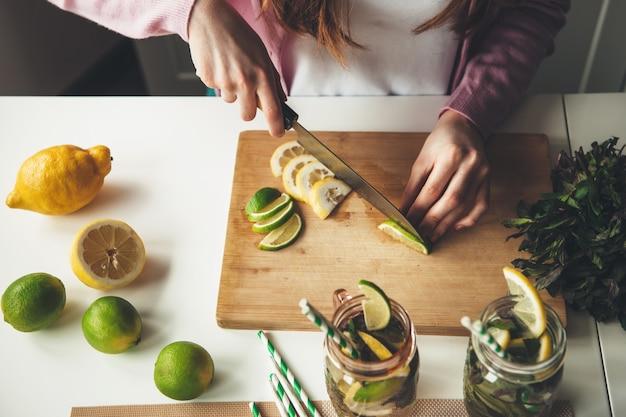 Bovenste meningsfoto van een vrouw die fruit snijdt en een mojitodrank maakt van citroen en limoen