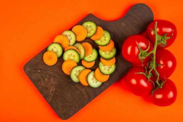 Bovenste plakjes wortel en komkommer met tomaten op houten snijplank op oranje