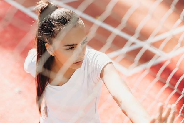 Bovenste portret van charmante jonge vrouw rusten na het hardlopen in de ochtend.