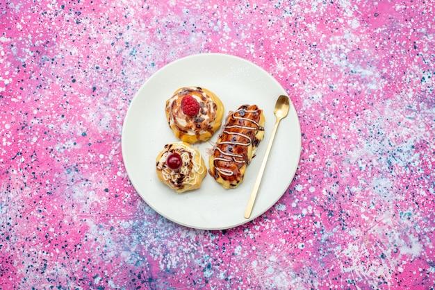 Bovenste verre weergave heerlijke fruitige taarten met room en chocolade in witte plaat op de roze achtergrond cake koekje zoet bakken
