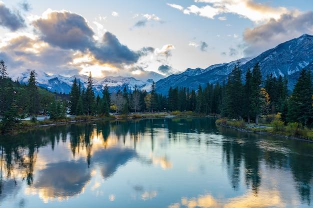 Bow river rivieroever in herfst seizoen zonsondergang tijd prachtige vurige wolken reflecteren op het wateroppervlak