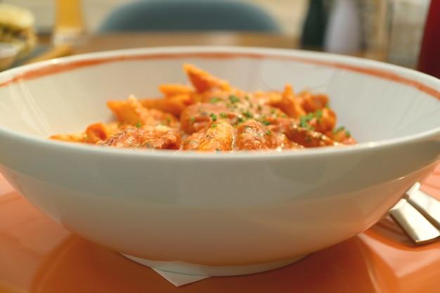 Bowl van penne pasta met garnalen en pittige arrabbiata saus