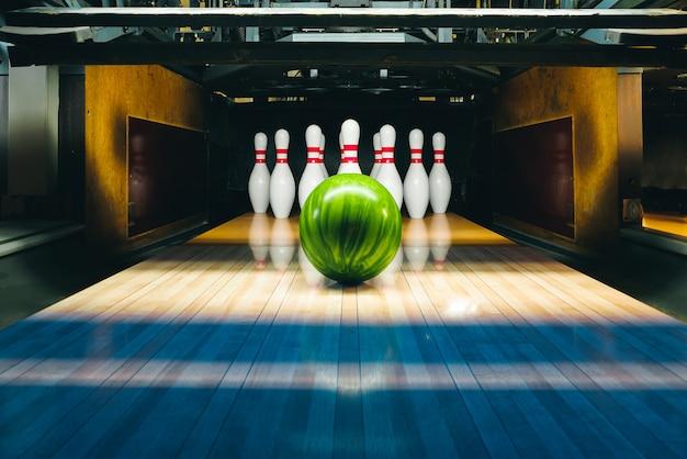 Bowlingbaan met groene bal en pinnen