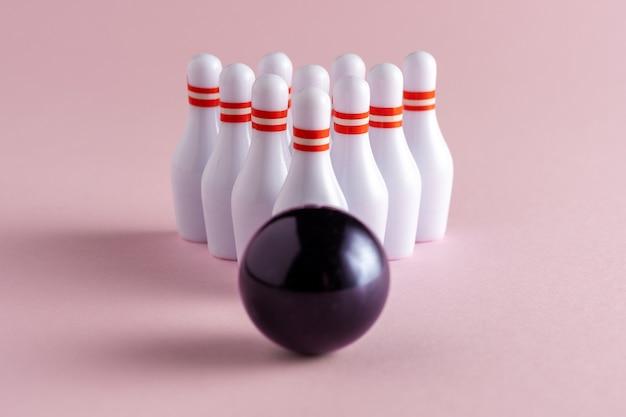 Bowlingbal en witte kegels op pastel roze achtergrond.