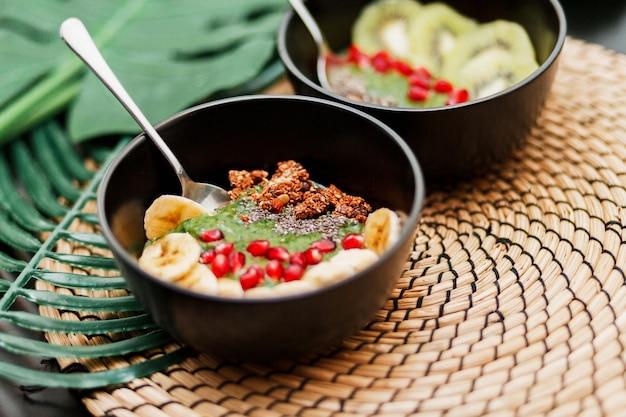 Bowls belegd met kiwi, granola, granaat, chia en avocado