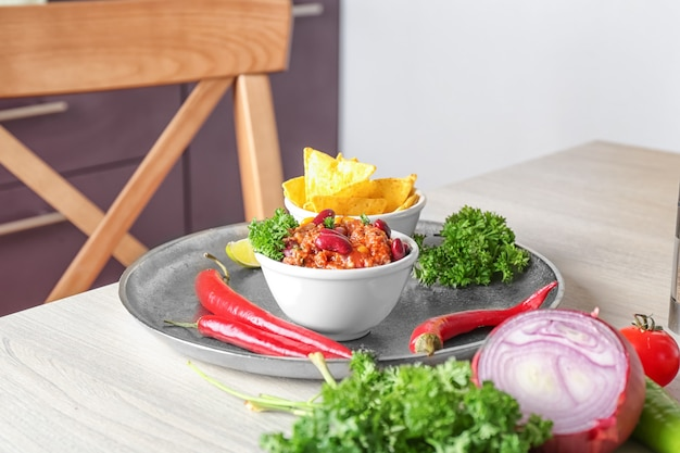 Bowls met chili con carne en nacho chips op metalen dienblad