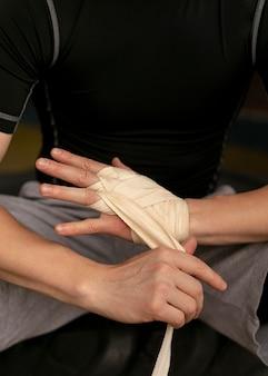 Boxer die zijn handen met bescherming inpakt voordat hij gaat trainen