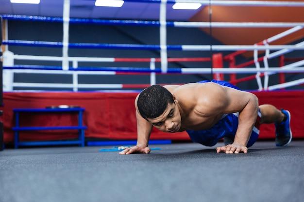 Boxer doet push-ups in de buurt van boksring