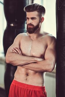 Boxer met blote torso leunt op de bokszak.