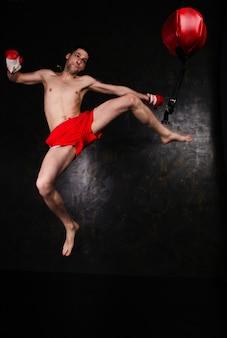 Boxer met rode handschoenen in donkere kamer